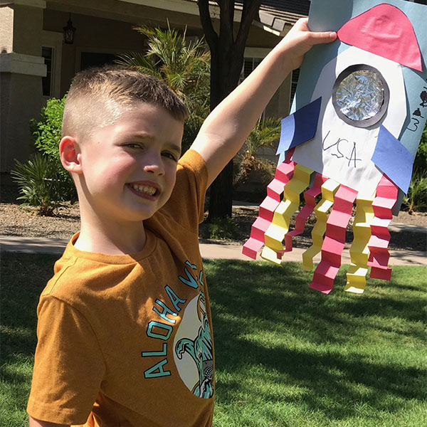 Young boy holding up a USA space rocket art project he created