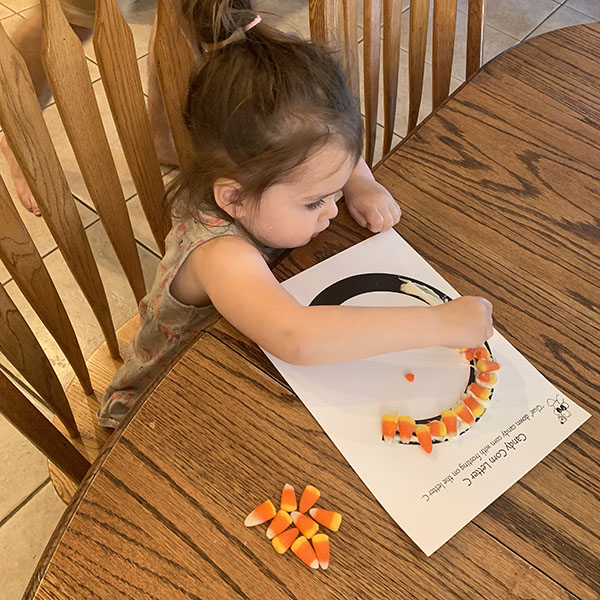 """Young girl gluing candy corn to a large letter """"C"""""""