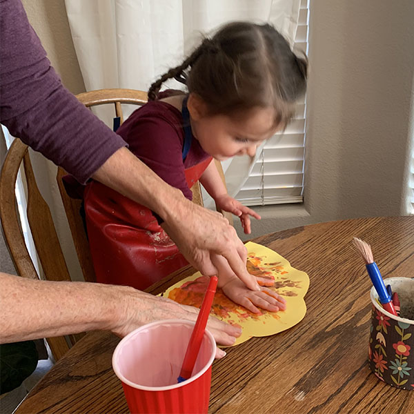 Young girl painting a turkey image with her hands