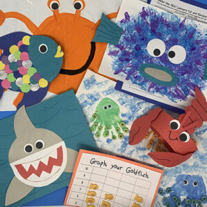 Under the sea projects compiled together showing a shark cut out, a lobster hat, a fish with many scales, and various worksheets