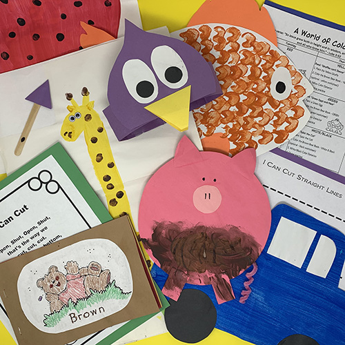 """World of color projects compiled into a group, including a painted """"muddy"""" pig, a goldfish, a penguin hat, and various worksheets"""
