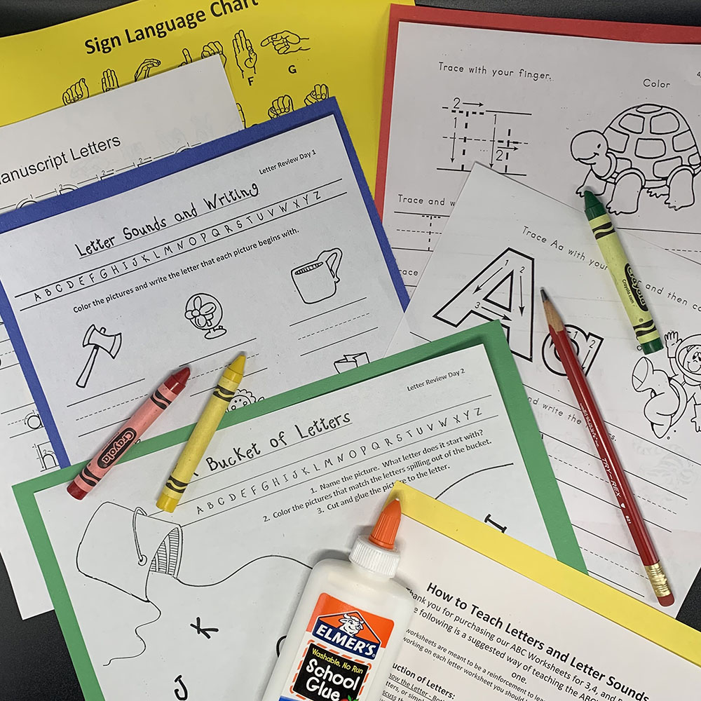 Several worksheets spread about on a table showing individual letters for writing practice