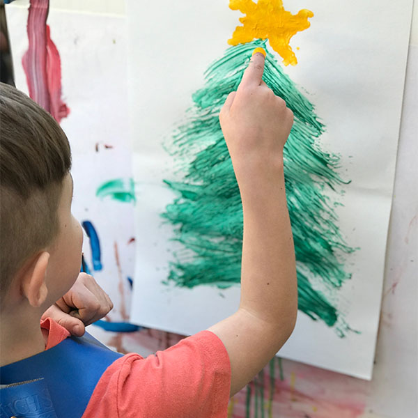 Young boy finger painting a christmas tree