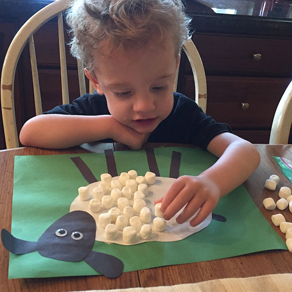 Child putting marshmallows onto a painted lamb for 3d fur effect