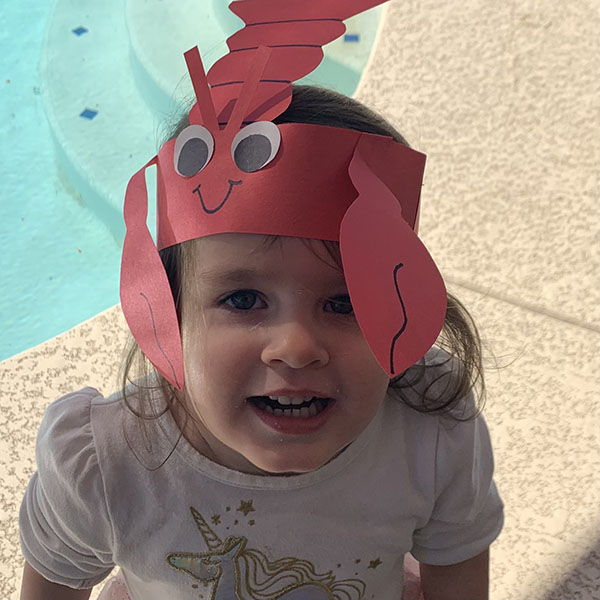 Young girl with a construction paper lobster hat