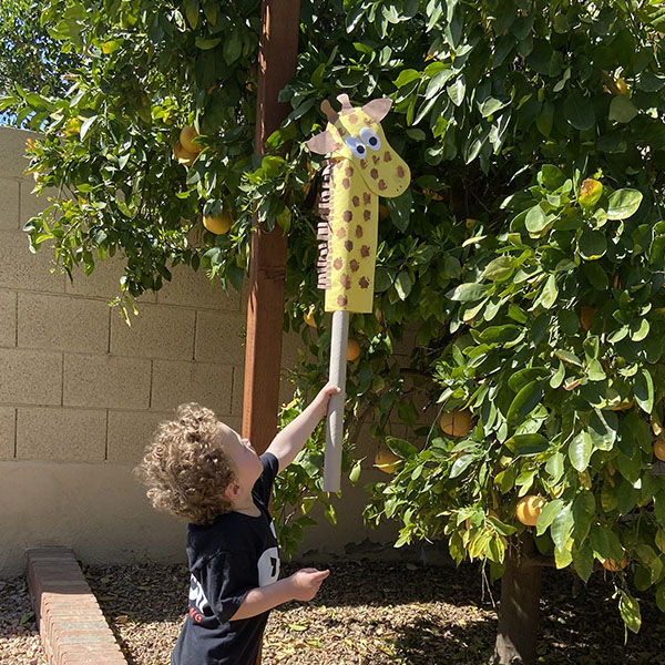 Young boy holding a giraffe art project up into a tree