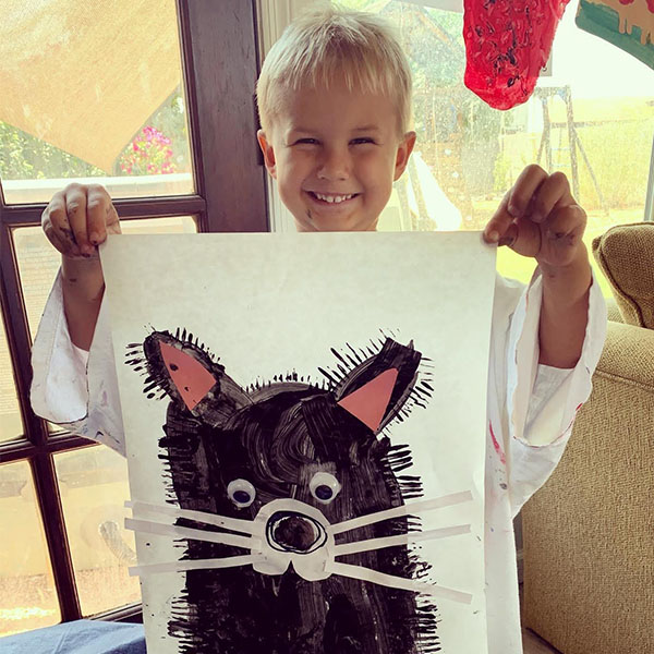 Young boy holding up a construction paper and paint art project he created